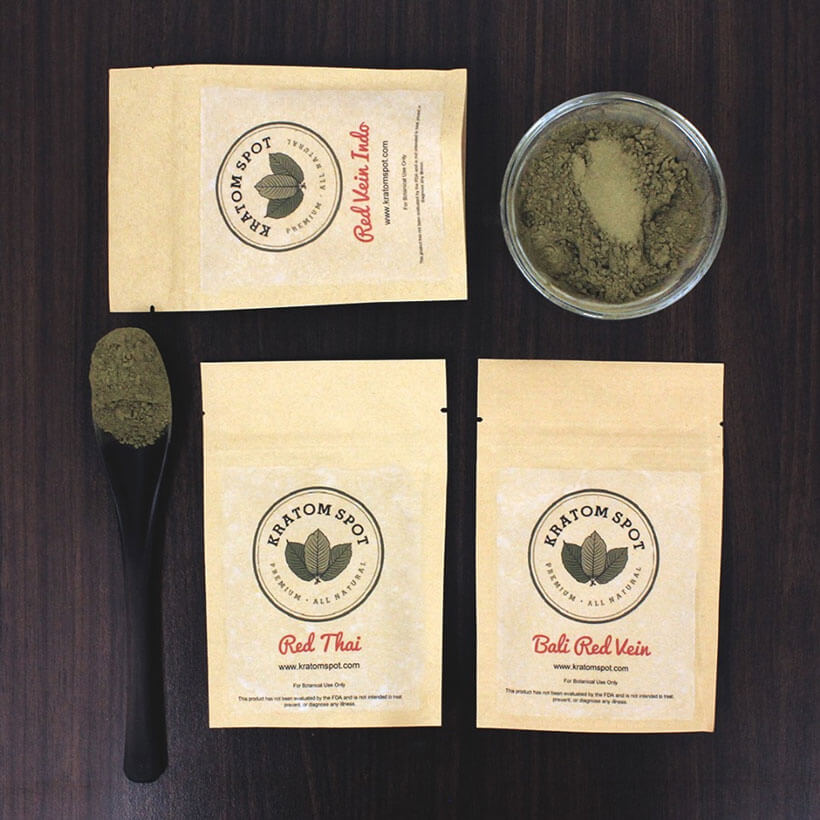 Several pouches of red Kratom and a bowl and spoon with powder in them